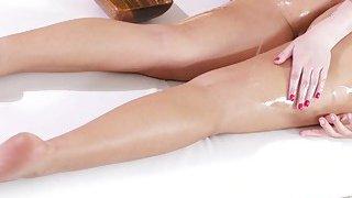 Naked tanned brunette gets lesbian massage